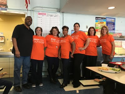 Faculty in matching orange shirts standing in the cafeteria