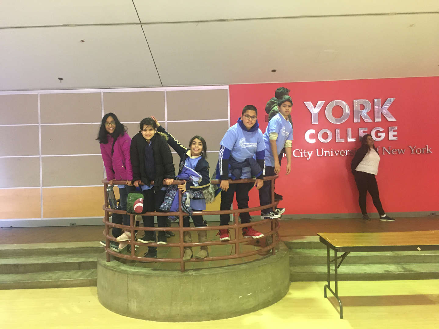Students stand on a railing in front of the York College sign