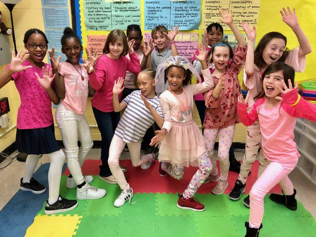 Girls wearing pink pose for a silly picture