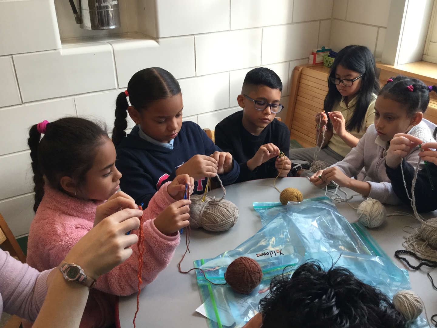 Students knit with yarn