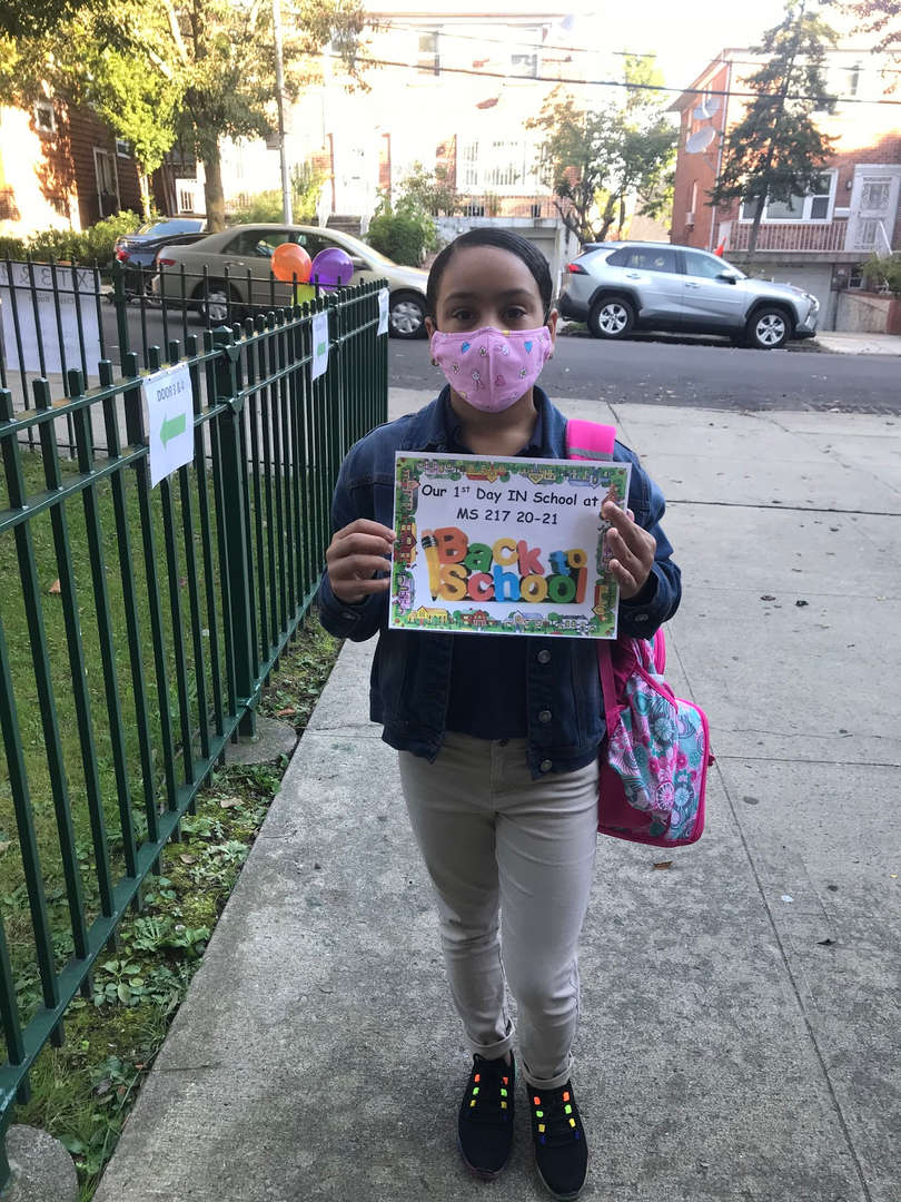 "Student wearing mask and pink backpack holding sign ""Our First day in School MS 217 20-21"""