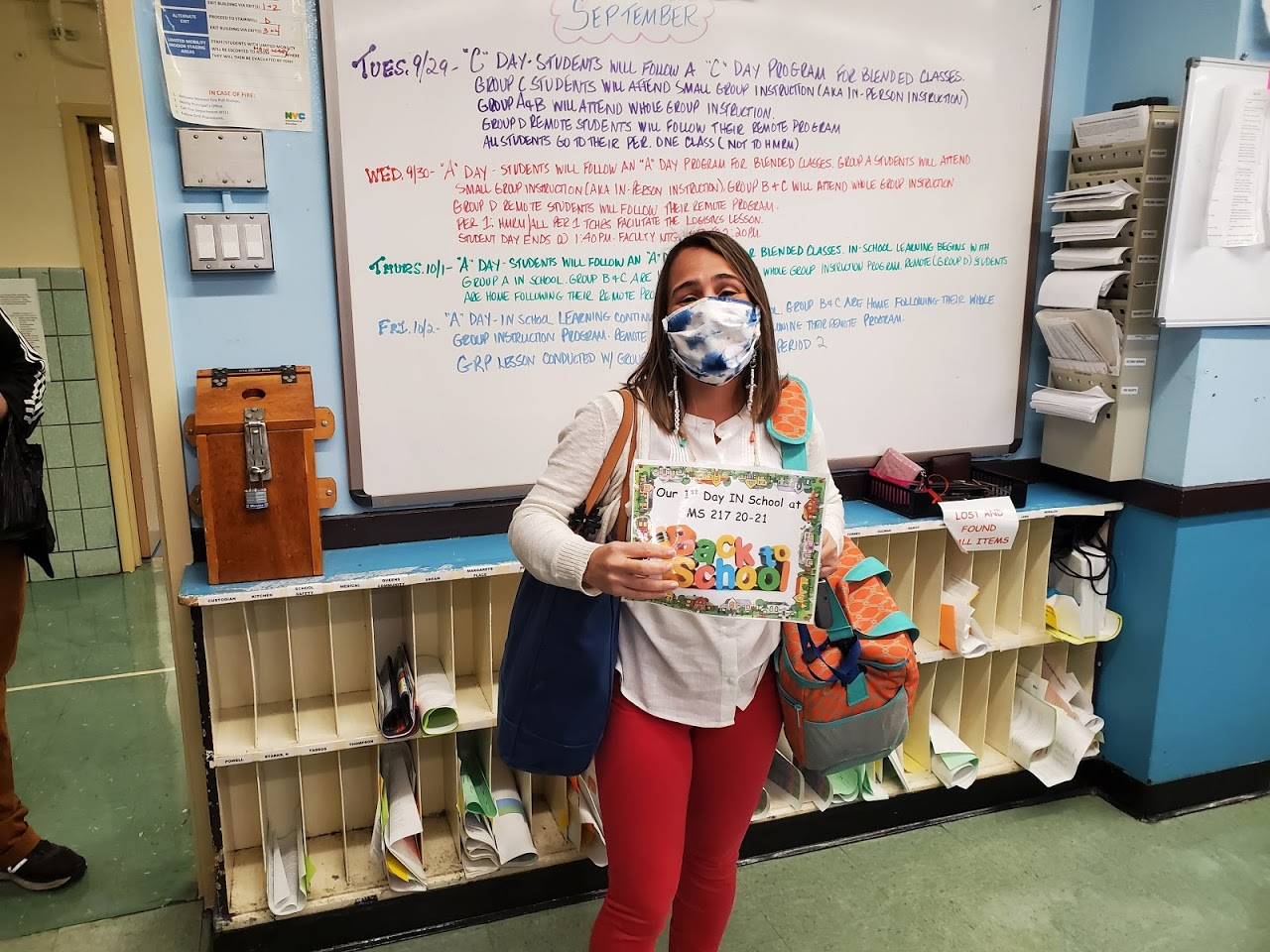 "Teacher wearing mask holding sign ""Our First day in School MS 217 20-21"""