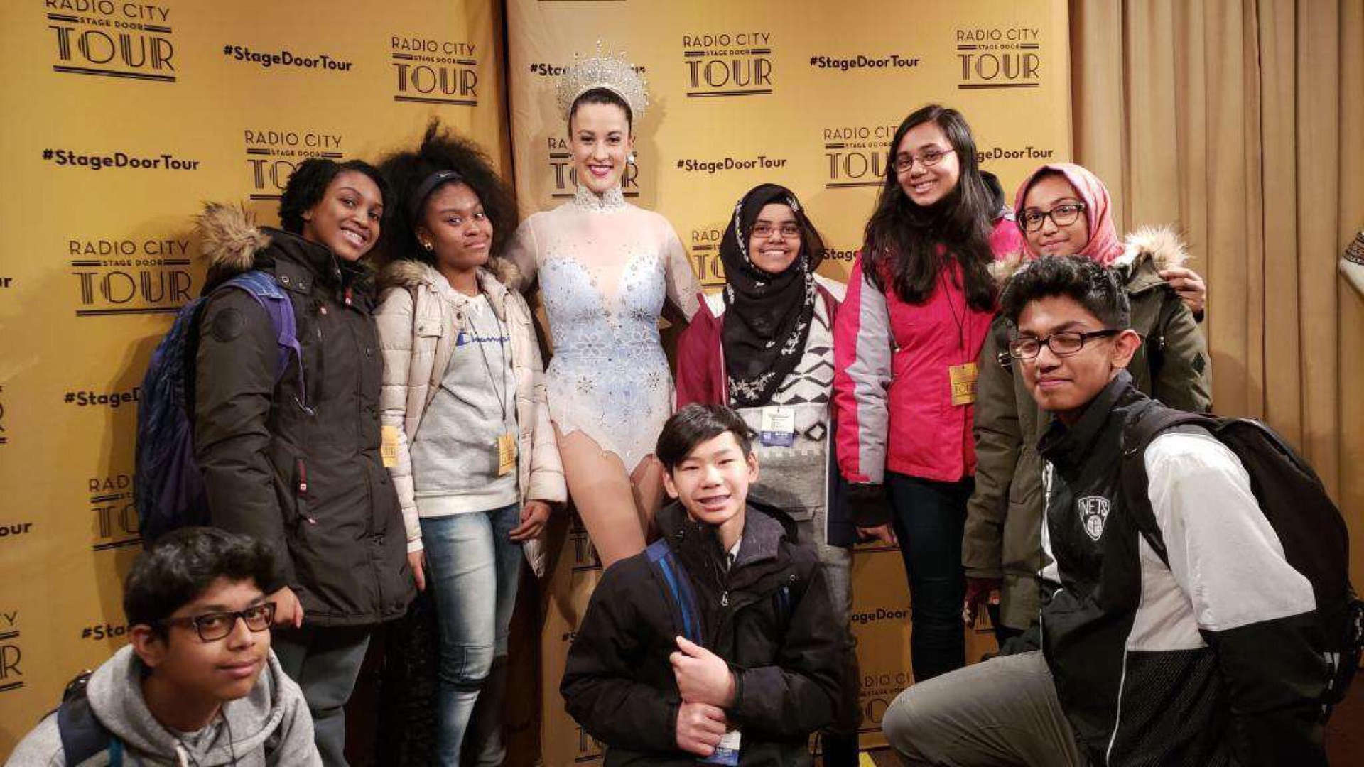Students pose with performer from Radio City Stage Door Tour