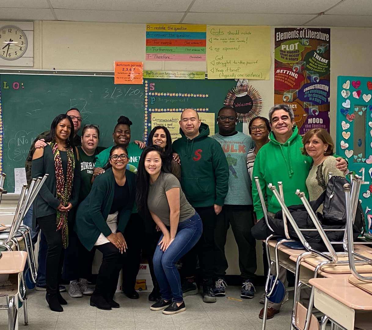 Teachers wearing green pose for a picture
