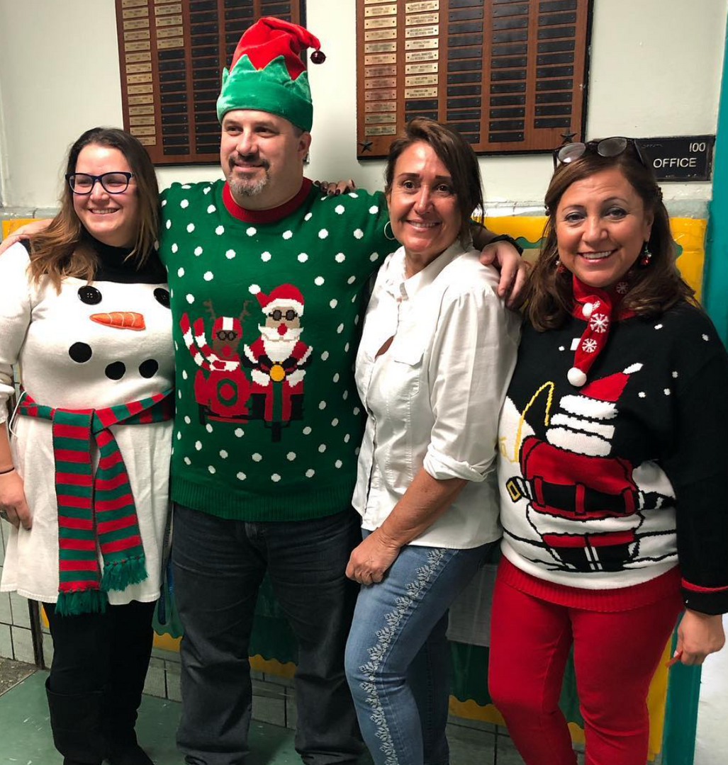 Teacher take a photo wearing Christmas sweaters