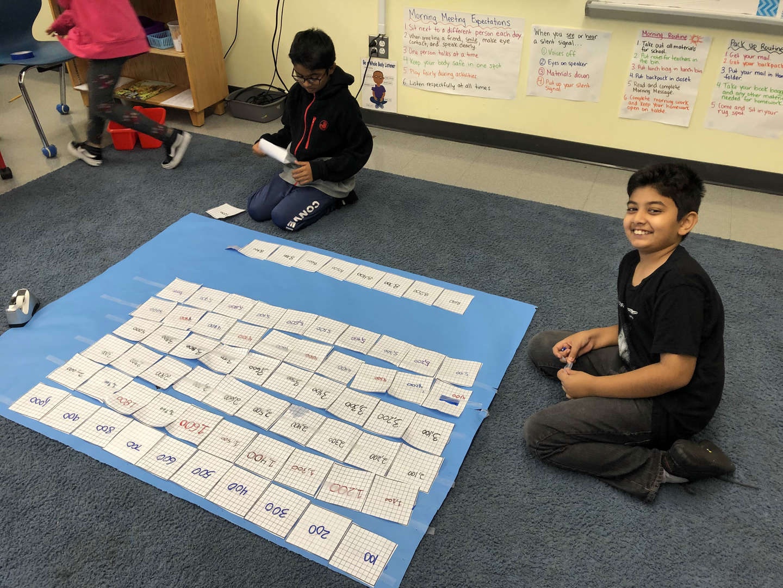 Student presenting math work he designed