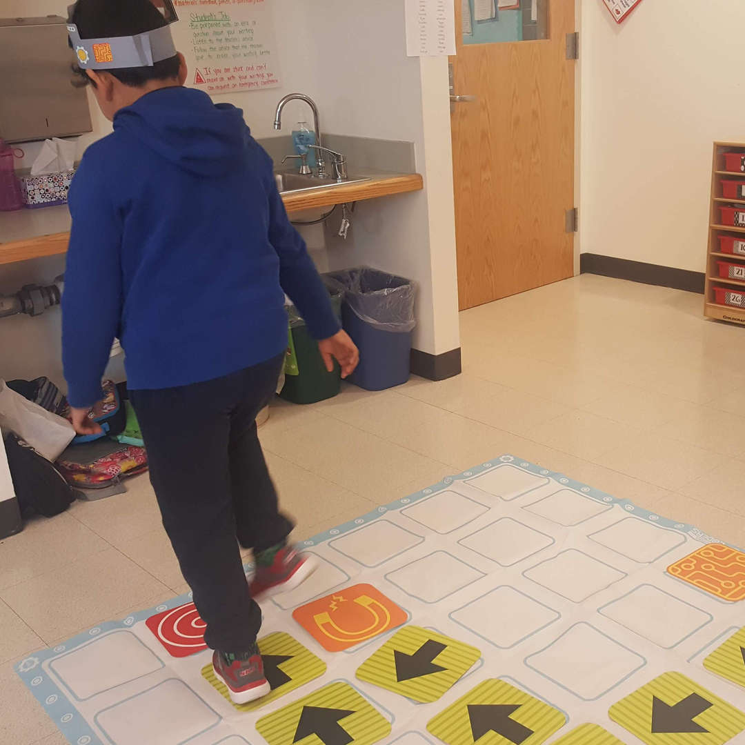 Student acting out a coding algorithm