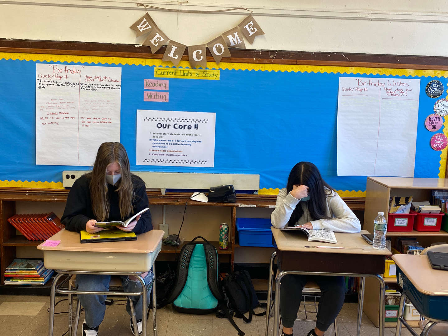 Two students wearing masks are shown reading books at their desks