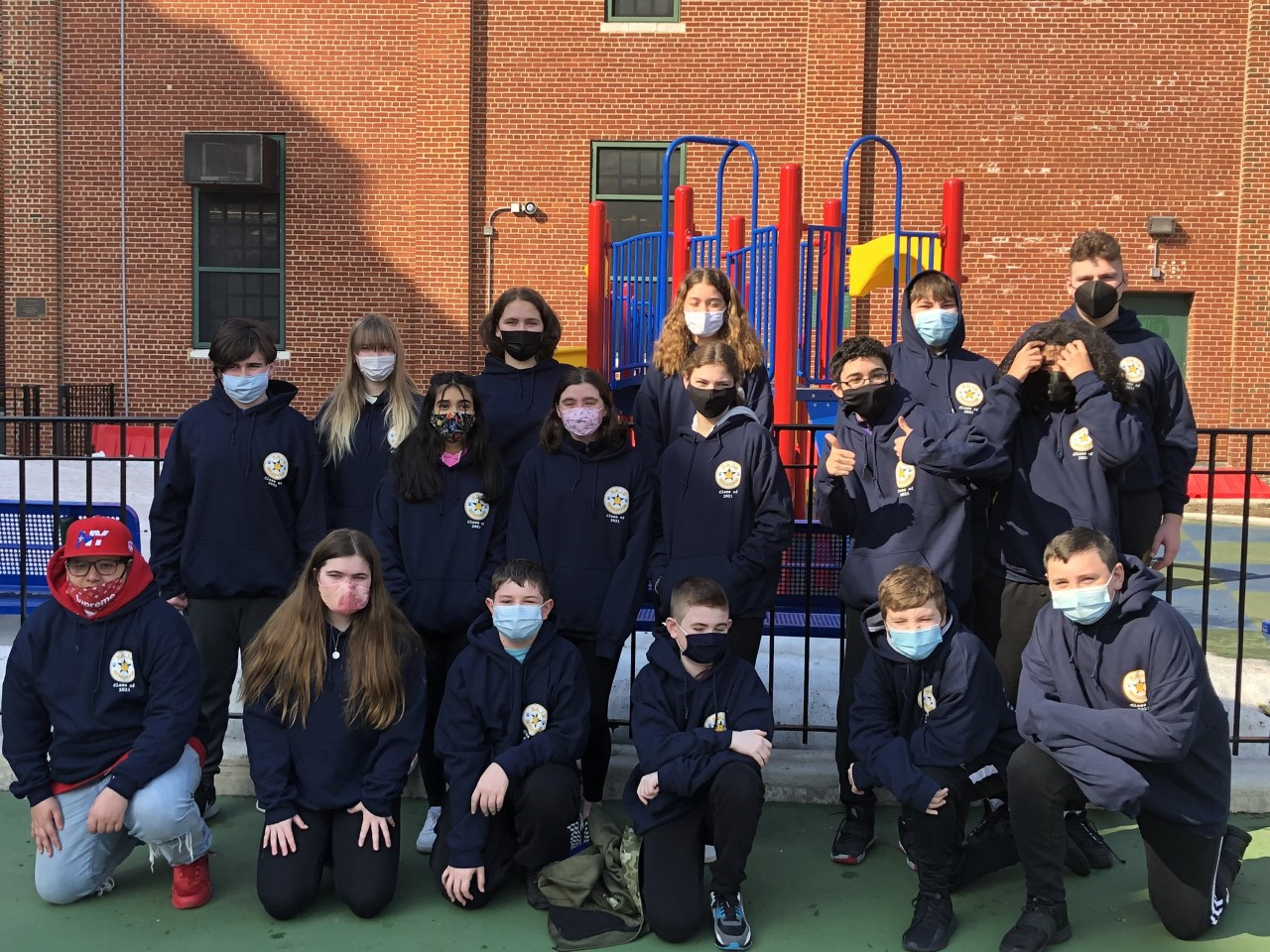 Students wear their school sweatshirts and face masks
