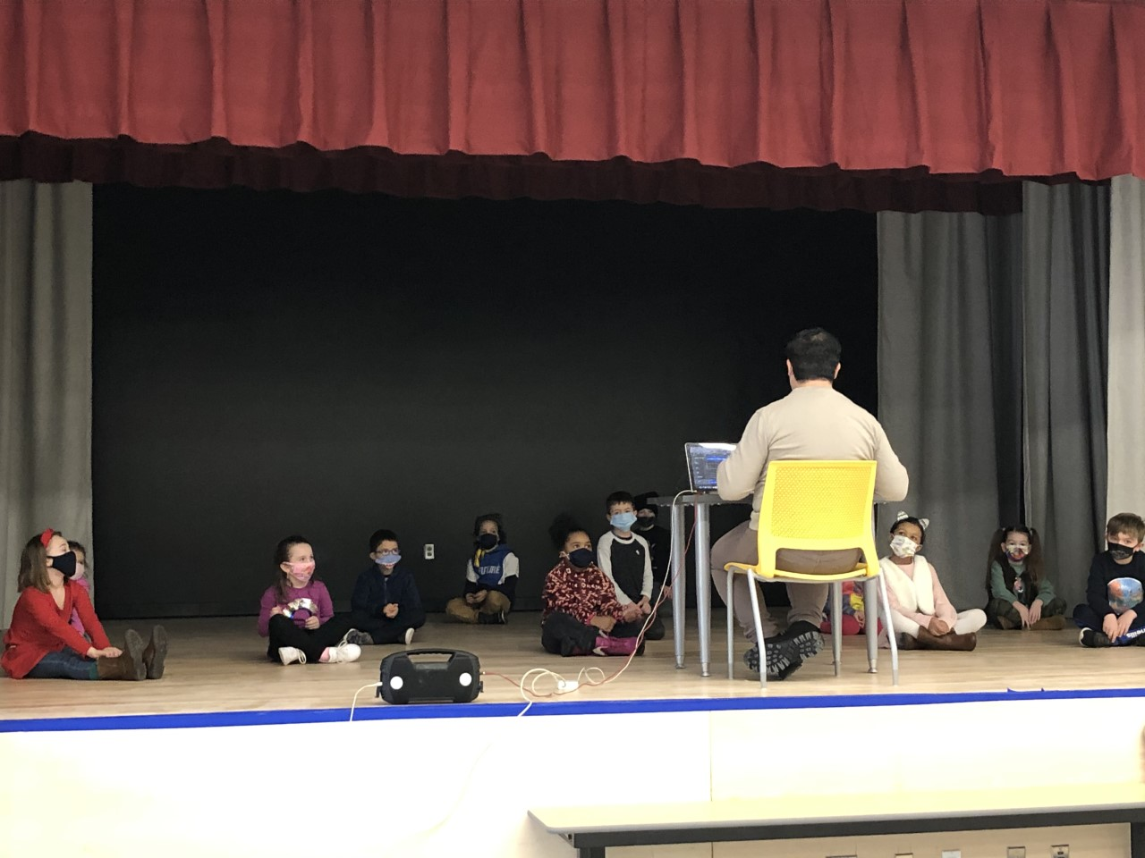 Students sit six feet apart on the auditorium stage