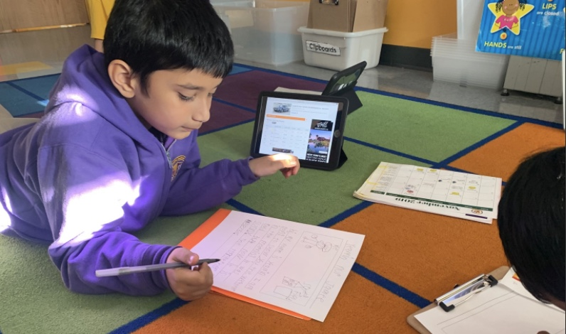 Student completes class worksheet using an iPad