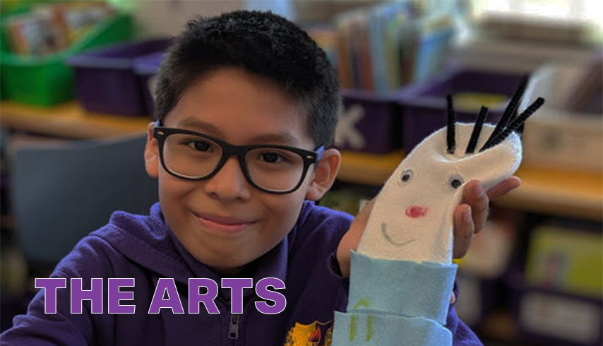 The Arts. Boy shows off arts and crafts project of a puppet made of felt and pipe cleaners