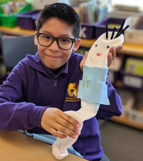Boy shows off arts and crafts project of a puppet made of felt and pipe cleaners