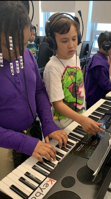 Students learn about music on the piano