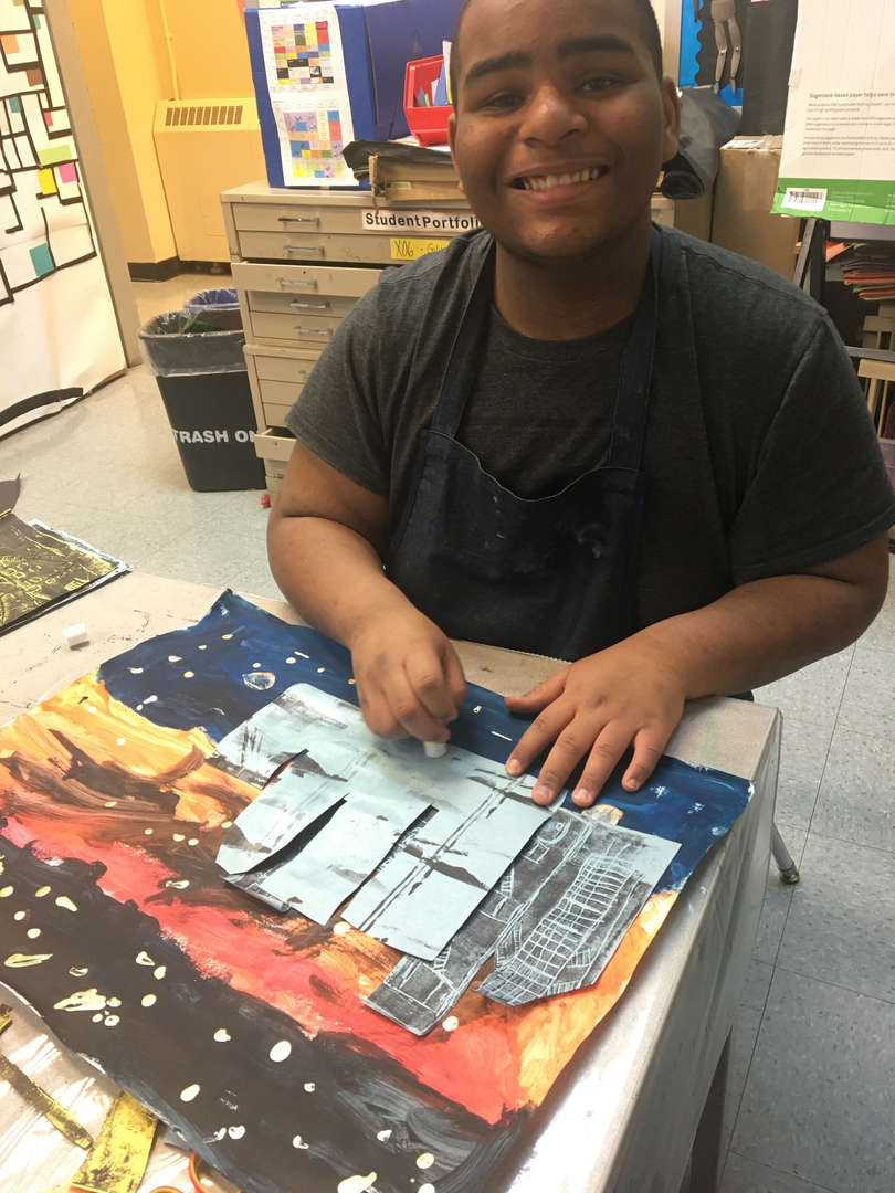 Student uses paint and construction paper for his art piece