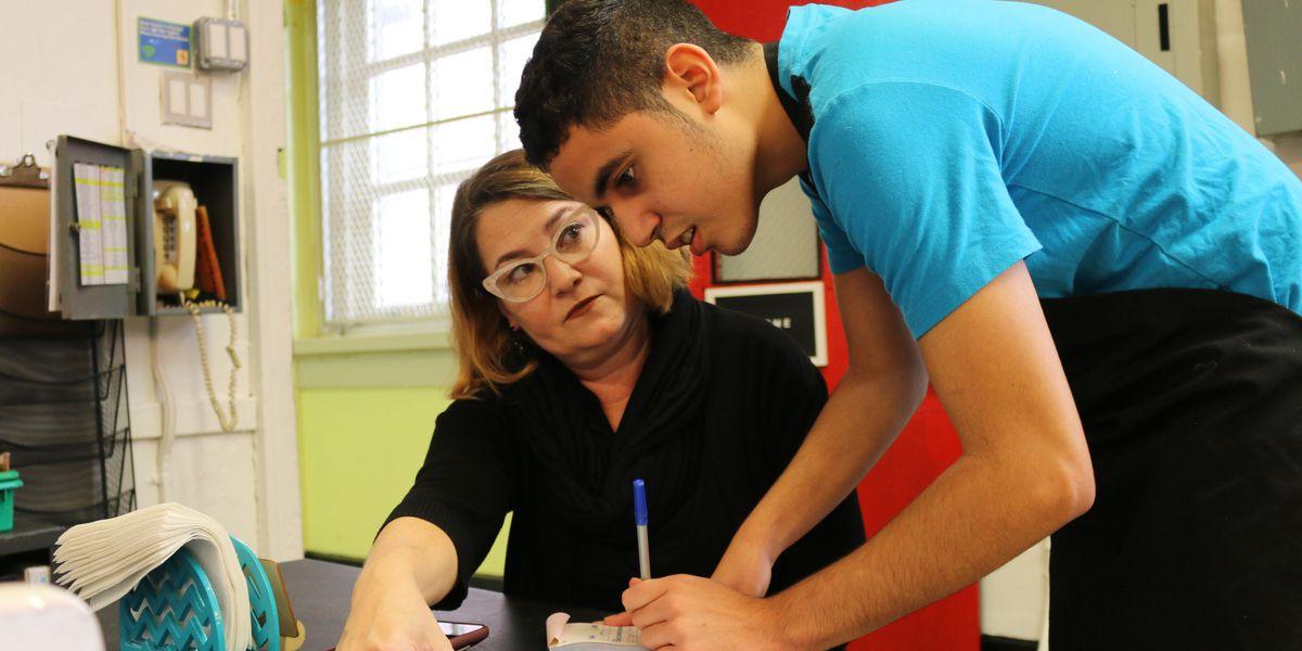 Teacher Guides Student Through An Assignment