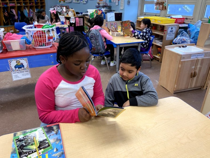 An older student peer reads with a younger student.