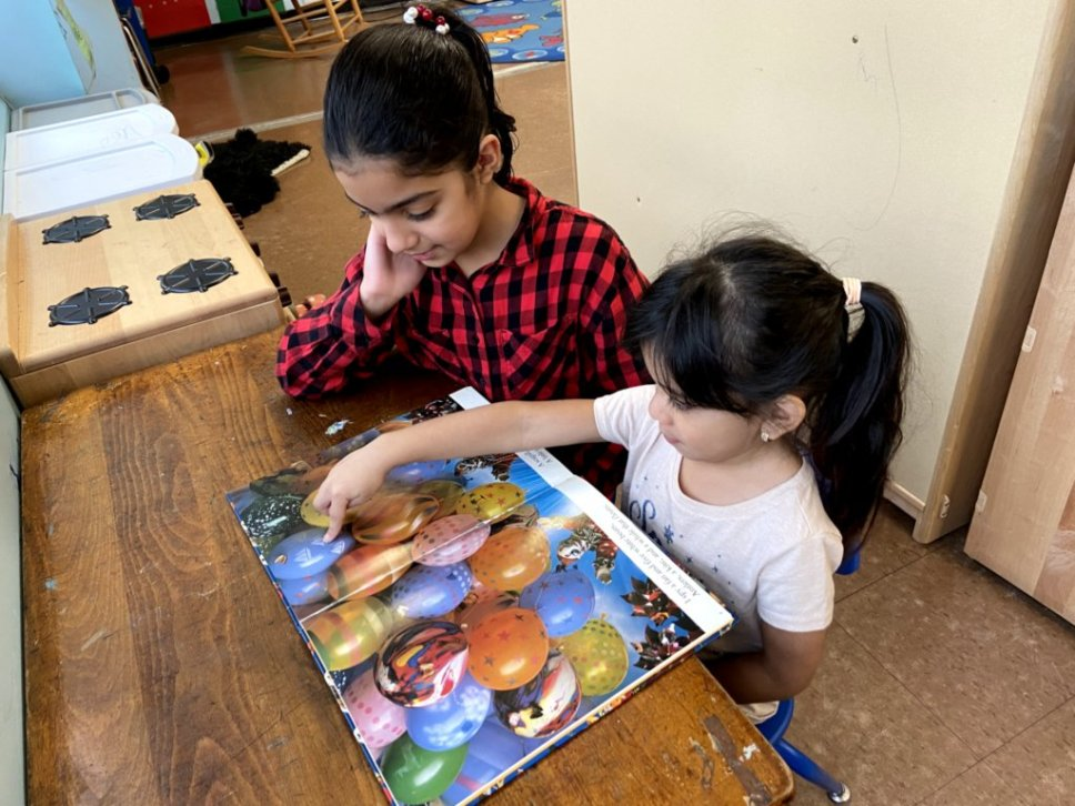 An older student helps a younger student with her reading skills.