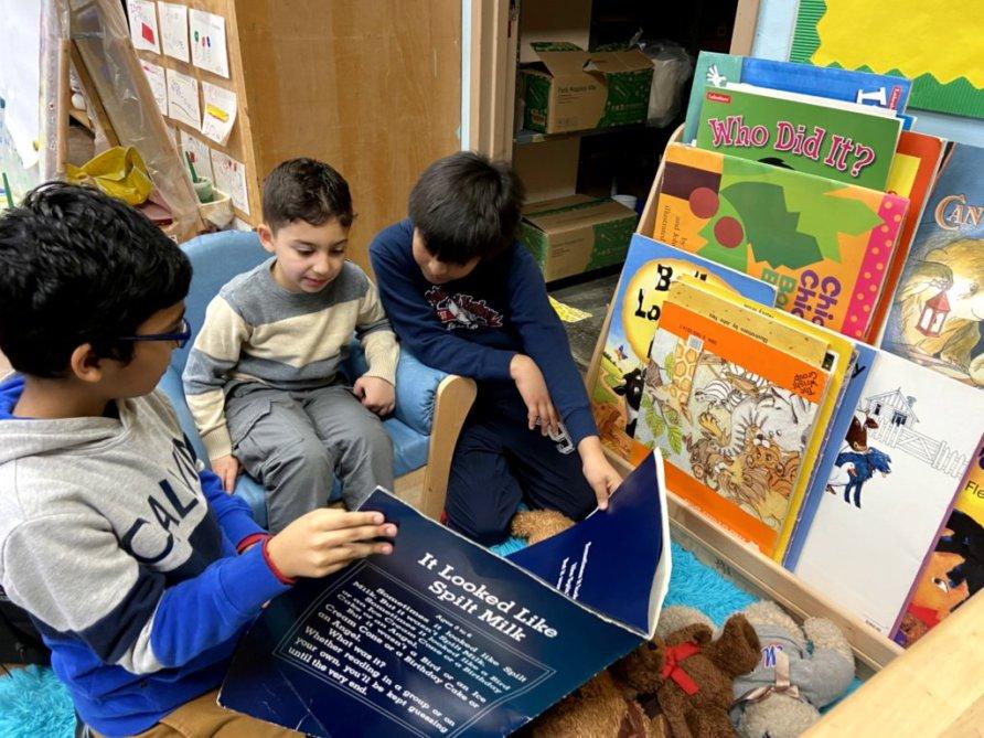 Three boys peer read together.