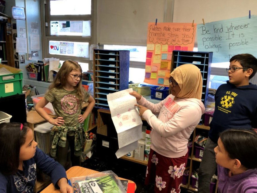 Student presents her class notes to a fellow group of students.