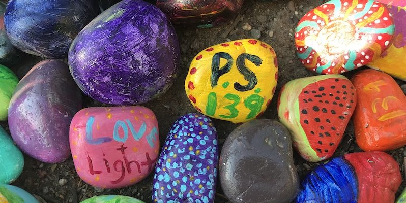 """""""PS 139"""" painted on colorful rocks."""