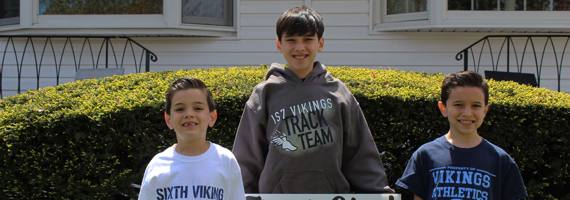 Three boys wearing I.S. 7 apparel smile for the camera.