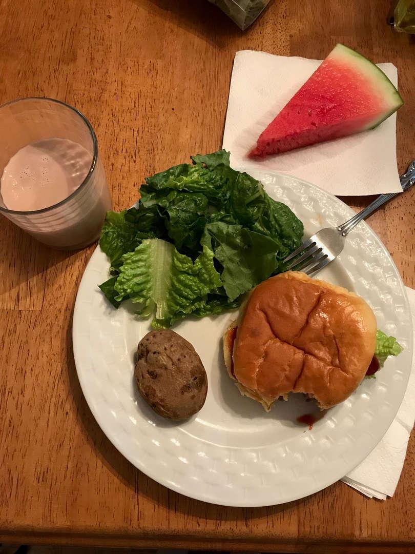 Hamburger, salad, potato, watermelon and chocolate milk