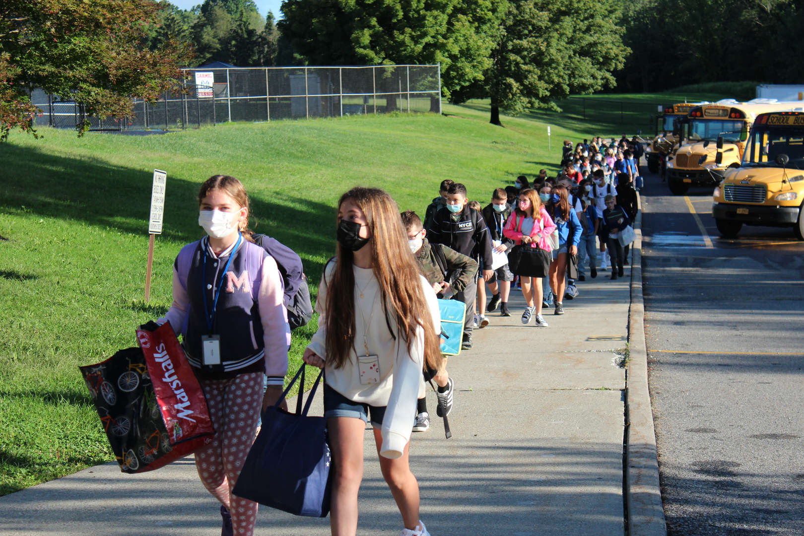Students enter George Fischer Middle School from buses