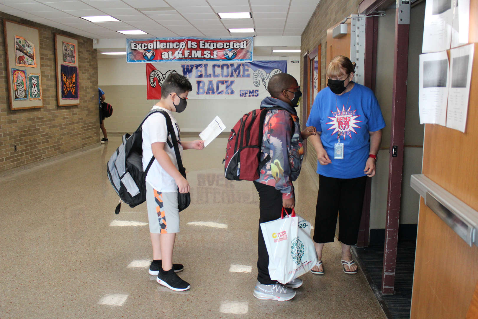 Students get help from staff entering the auditorium