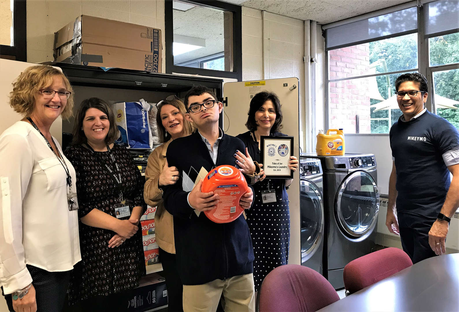 Student Michael Wishner poses with school administrators and teachers in the laundry room.