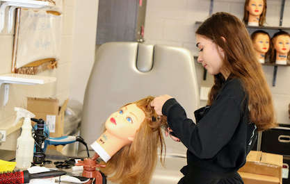 cosmetology student practices hair styling on a mannikin