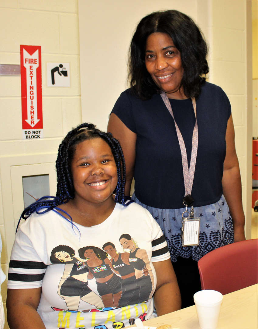 A student and staff member pose for a photo during the Spirit Week breakfast.