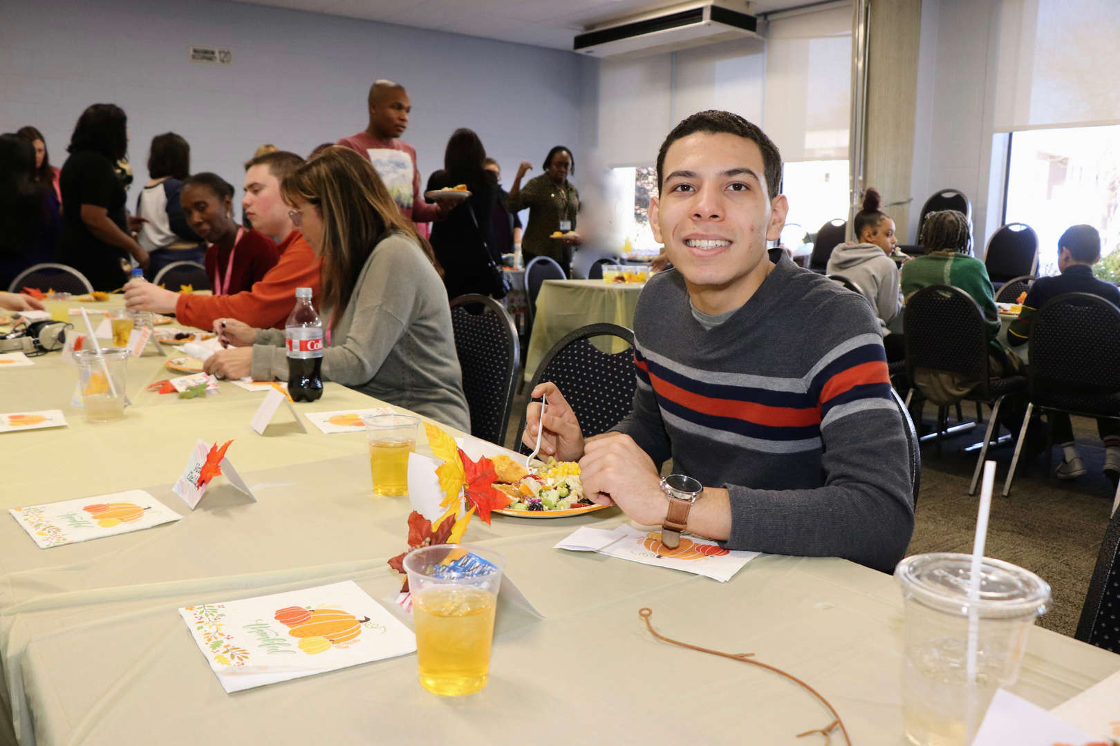 student smiles at Thanksgiving table