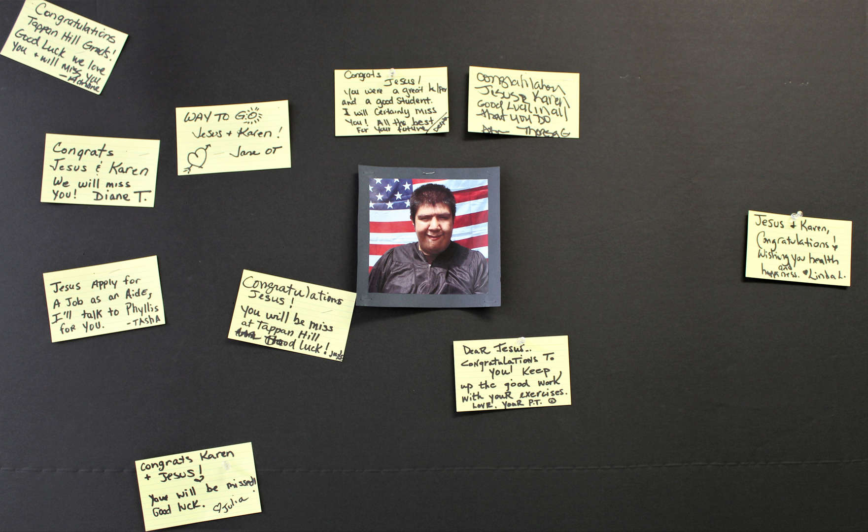 Bulletin board with picture of graduate Jesus and congratulatory messages.