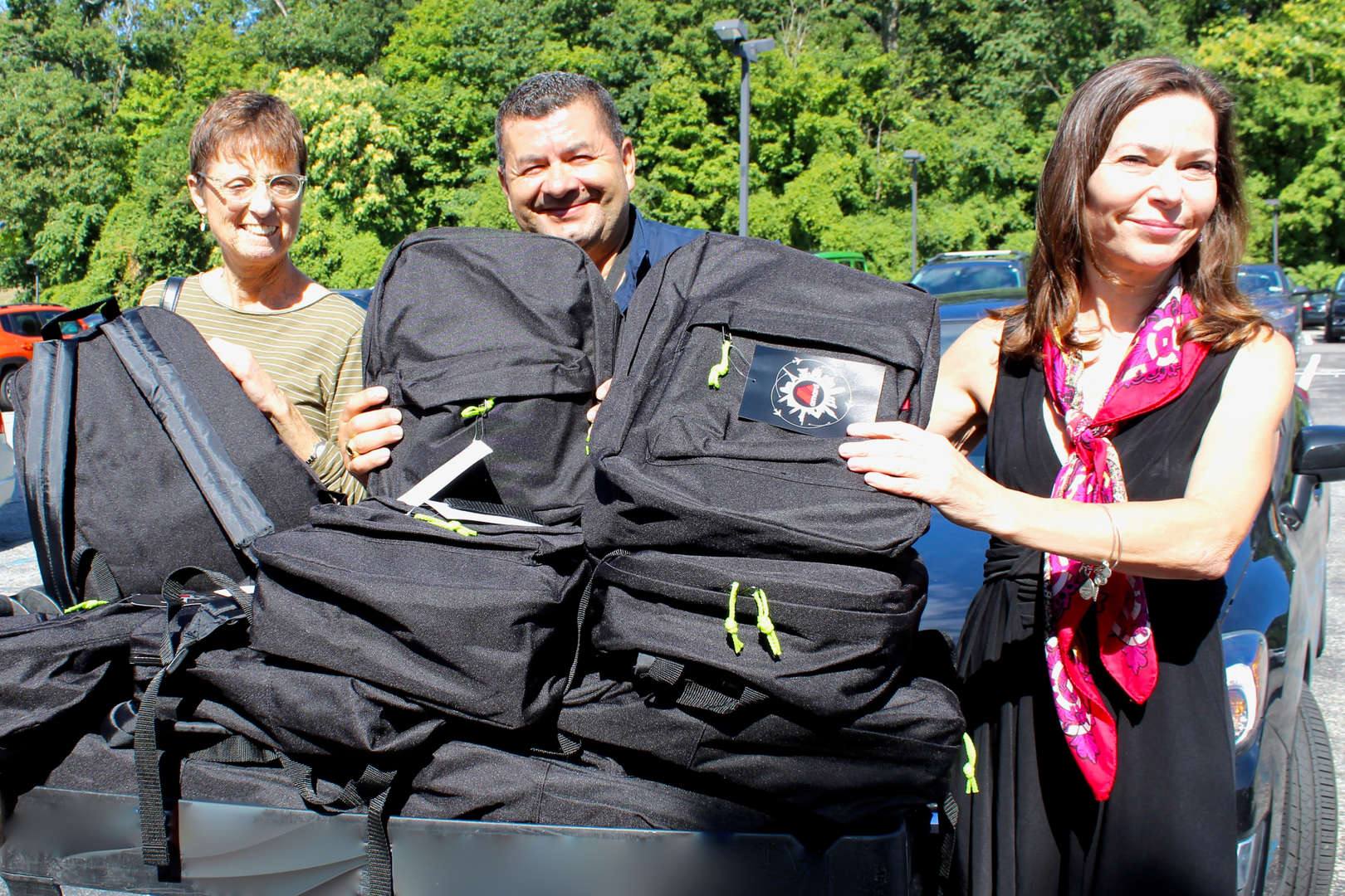 school officials receive backpack donation