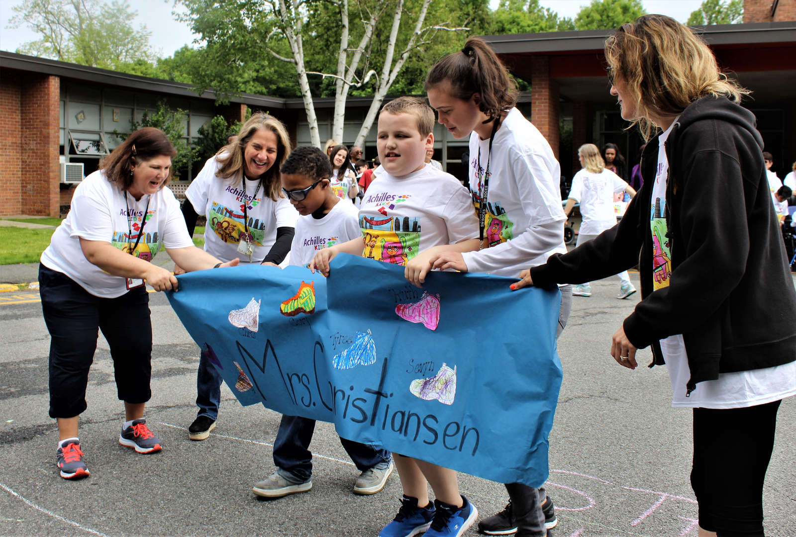 Students break through the banner at the finish line.