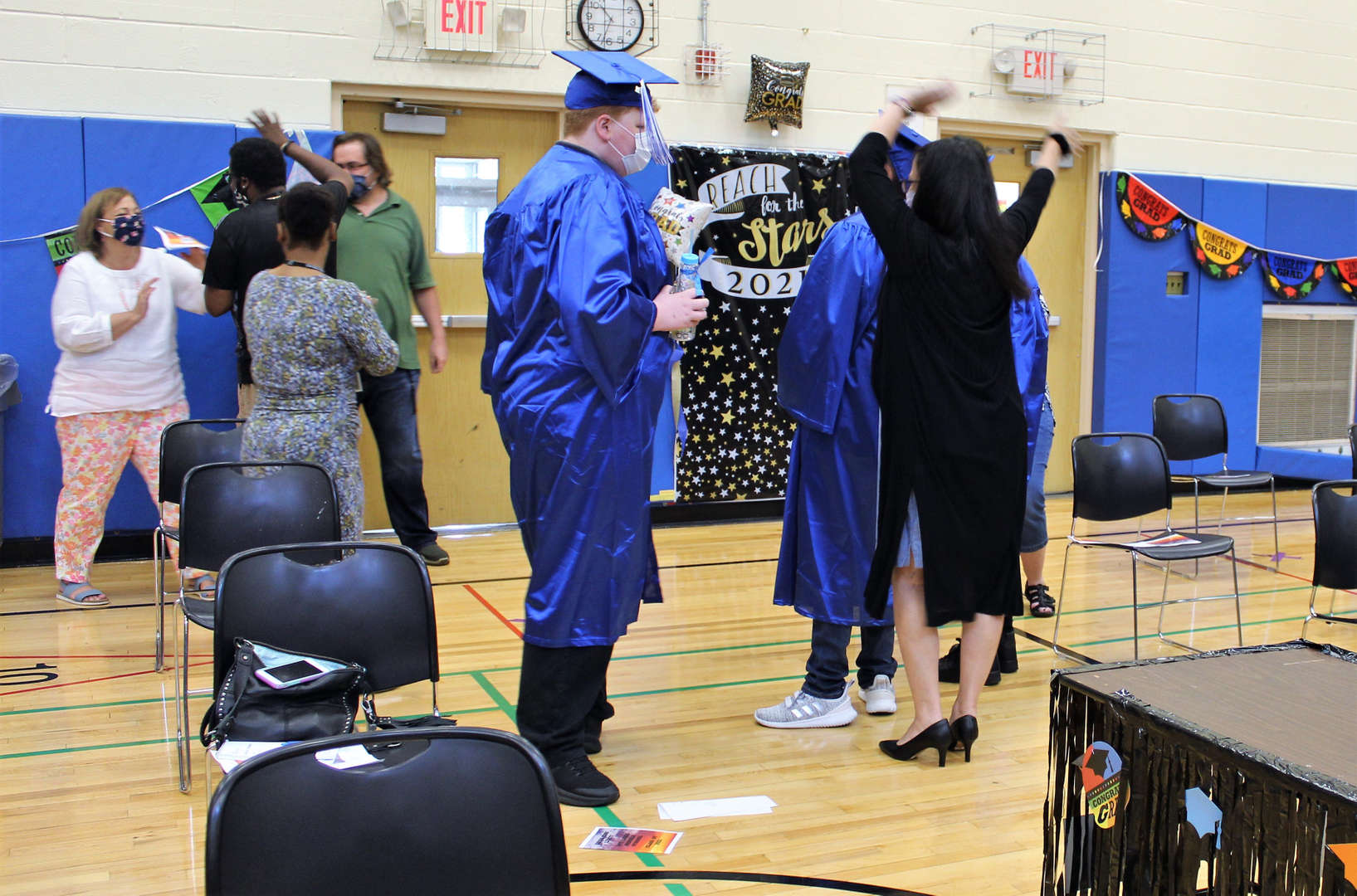 Graduates process out of the auditorium with teacher Tiziana DeMasi after the ceremony.