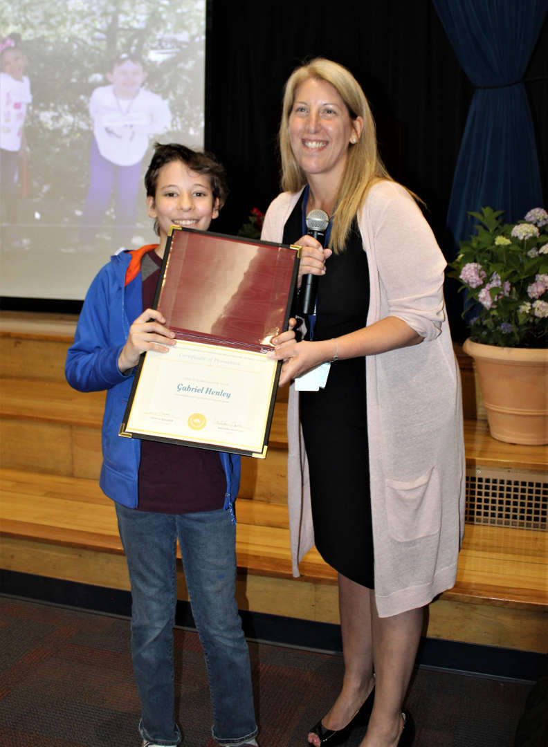 Student shows off moving-up certificate with the school principal.