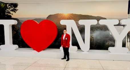 student poses in front of I heart NY sign