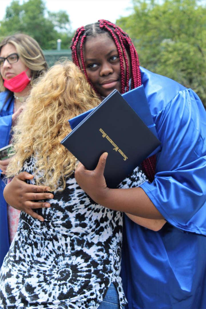 Tishari Goldstein-Brissett hugs a Rye Lake Campus staff member after the graduation ceremony.