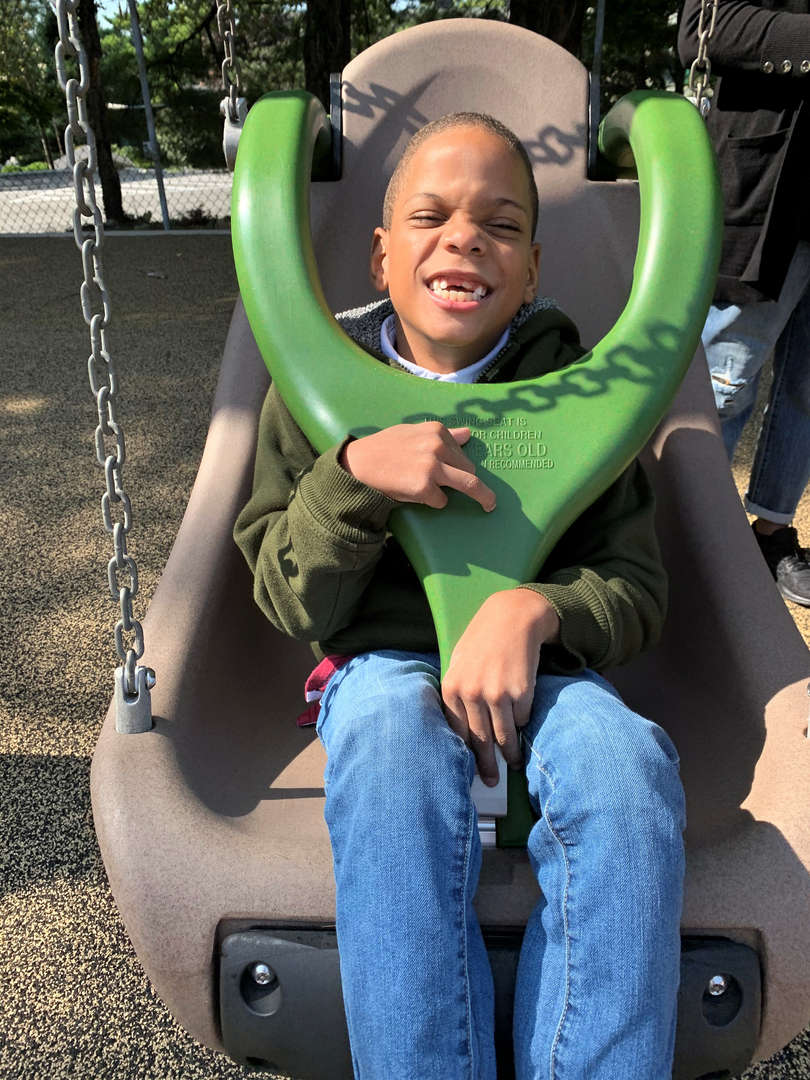 A boy has fun on a swing at the Tappan Hill School playground.