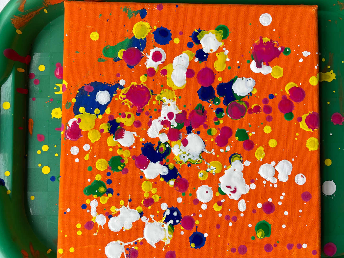 Pollock-style paint drops on orange canvass is complete