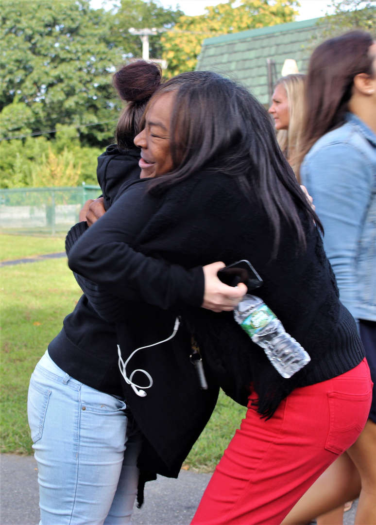 A staff member hugging a student.