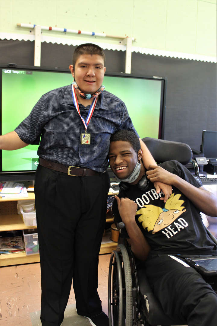 Graduate Jesus poses for photo with classmate Christopher Thompson.