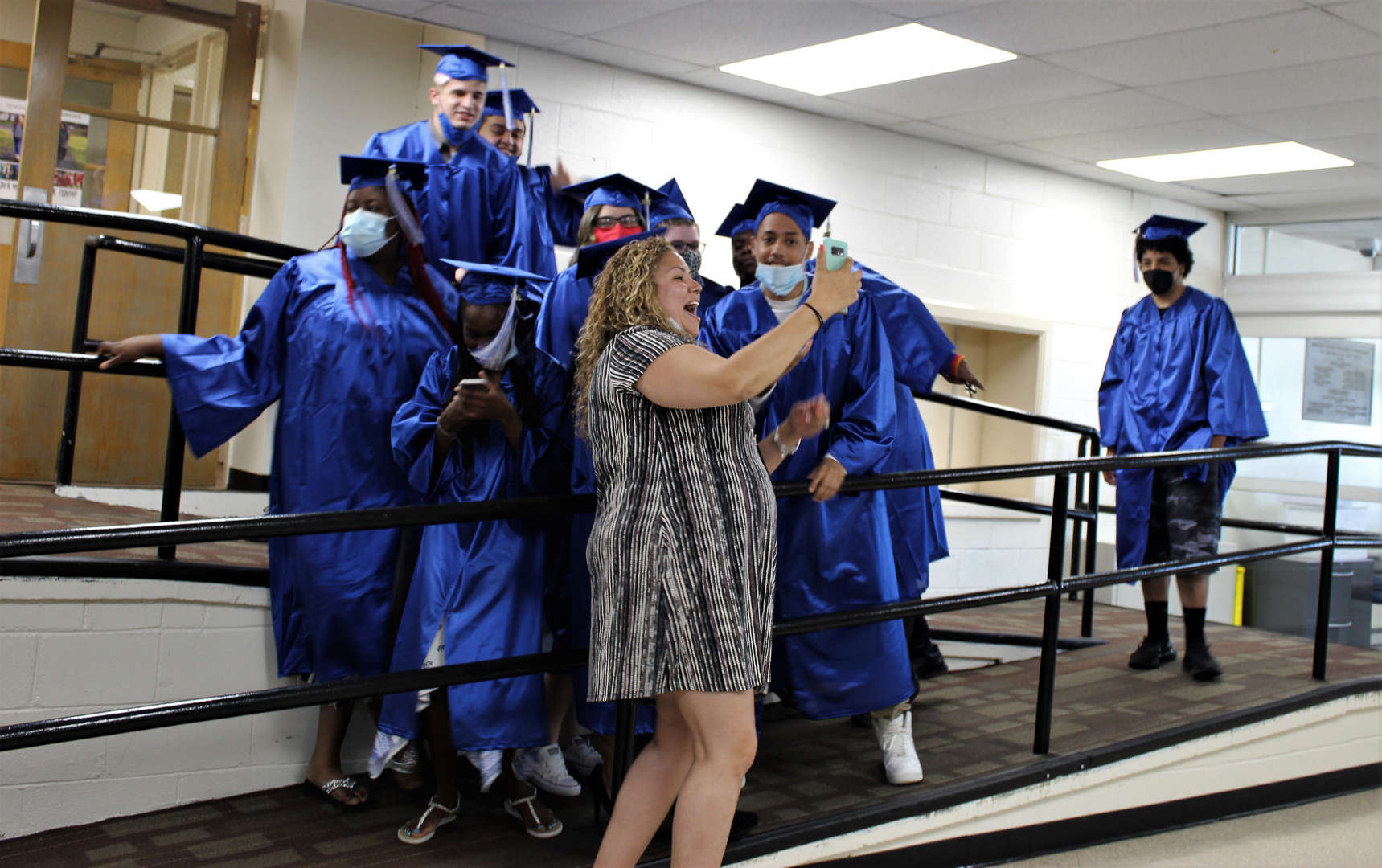 School counselor Cristina Tompkins takes a selfie with graduates.