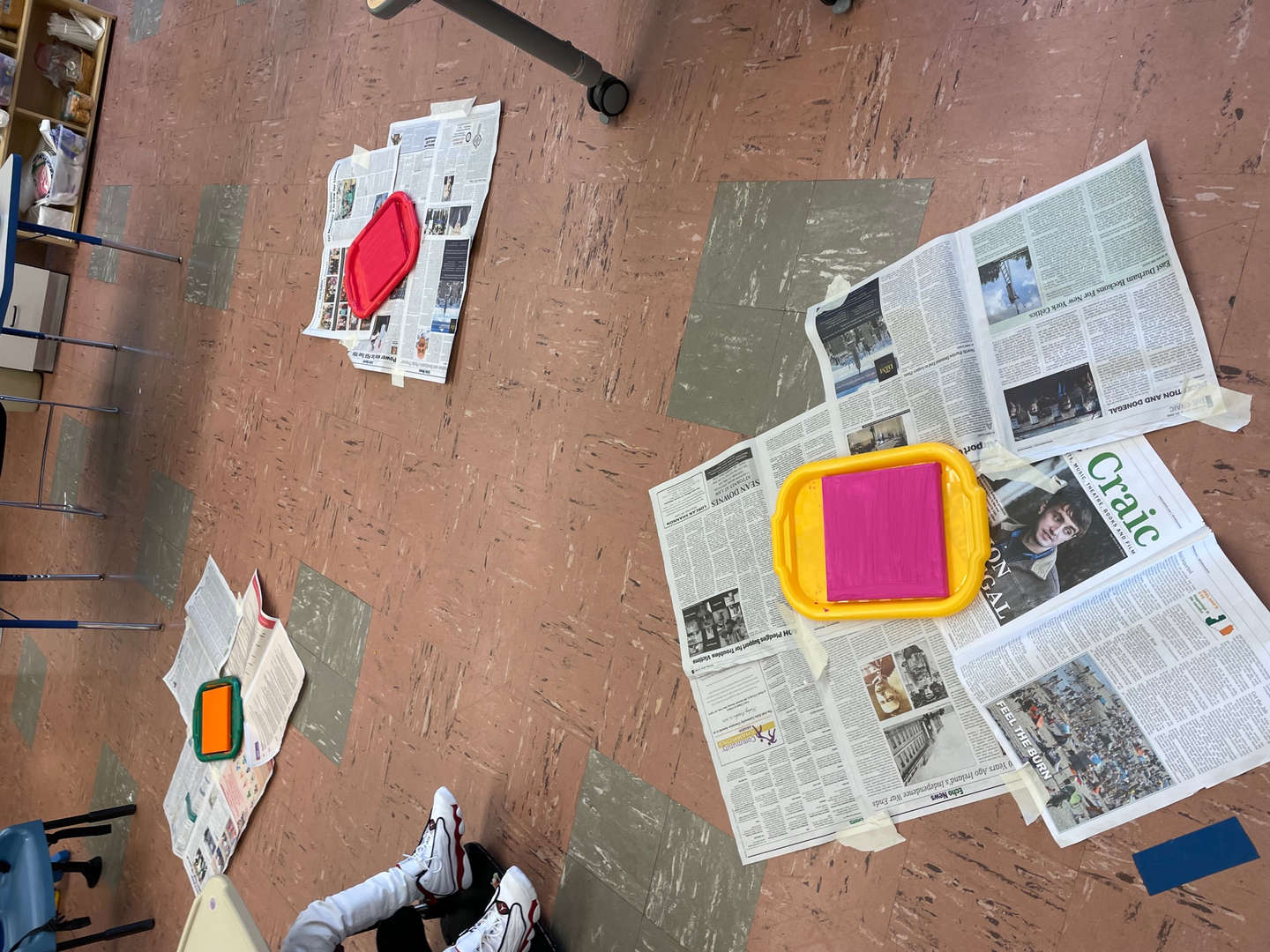 the artwork in progress laid out on newspapers to dry
