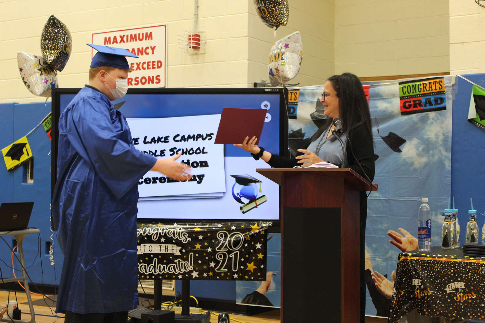 Graduate Declan Byrne accepts an award from teacher Tiziana DeMasi.