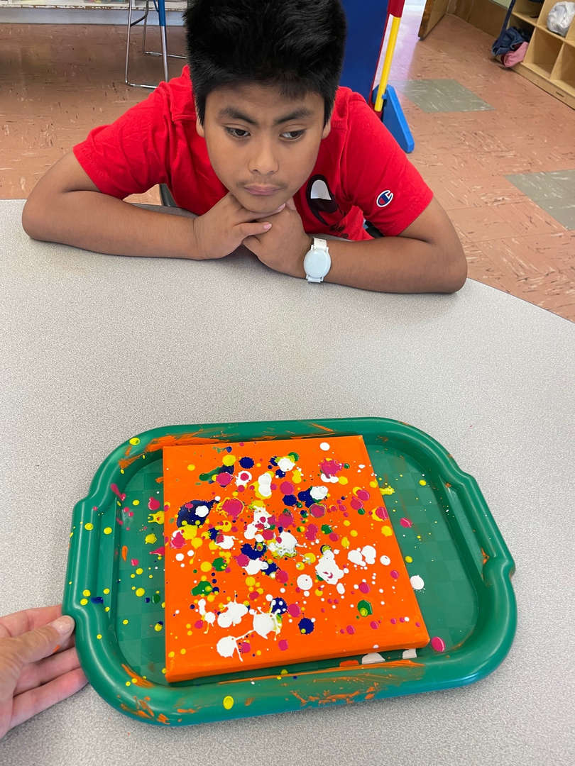 orange canvass with pollock painting by student