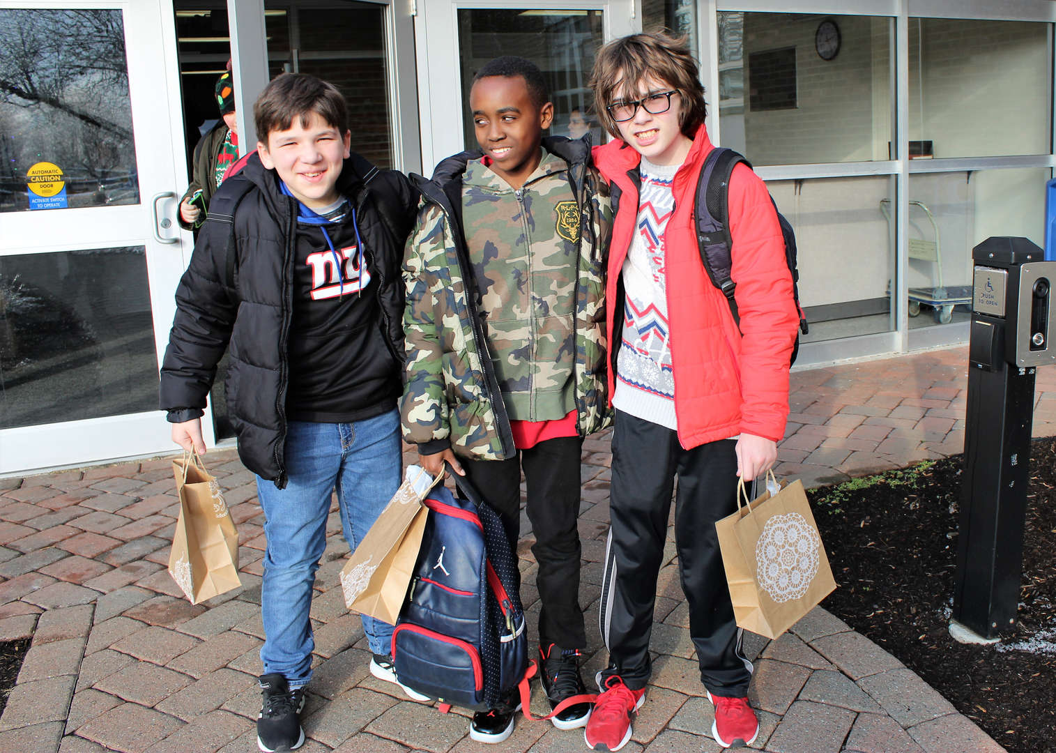 Three male students with the gift bags they received from staff.