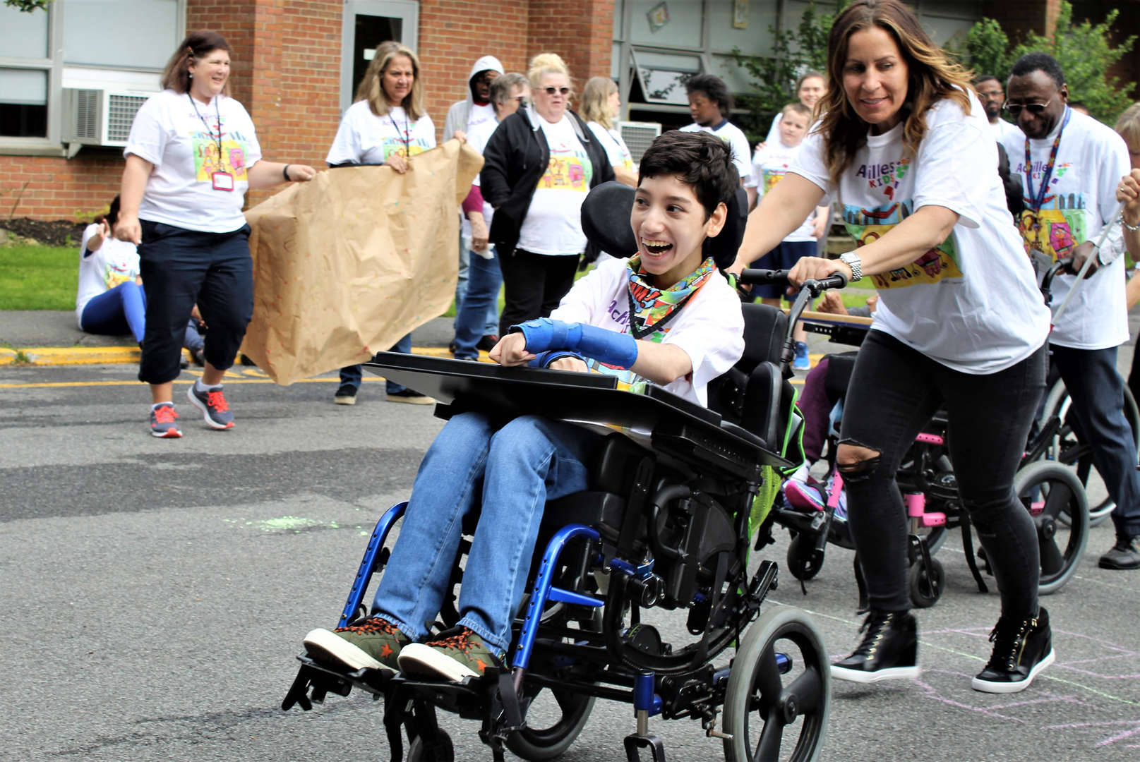 A staff member pushes a student in a wheelchair.